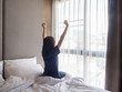 Woman stretching in bed after waking up, back view