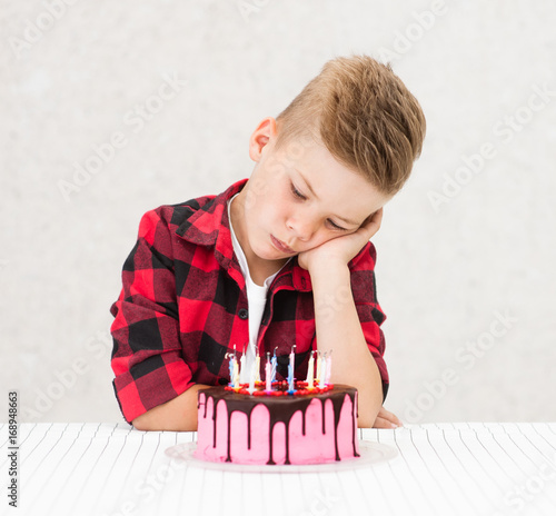 Sad boy sitting with cake with extinct candles Wall mural