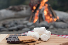 Smores Ingredients At A Beach Bonfire With Chocolate, Marshmellow, And Graham Crackers With Room For Copy