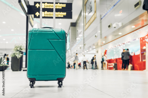 Photo sur Toile Aeroport Suitcases in airport departure terminal with traveler people walking in background,Holiday vacation concept, Business trip,selective focus on suitcases