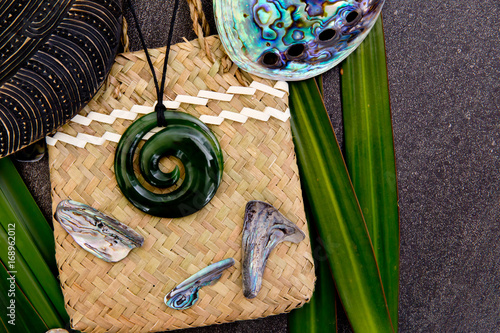 Foto auf Leinwand Ozeanien New Zealand - Maori themed objects - greenstone jade pendant on woven kite flax bag with shell pieces