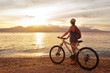 Traveler with bike enjoying the sunset on the background of the island