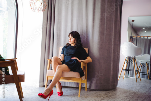 Young Attractive Woman With Long Legs In Black Elegant Dress Sits