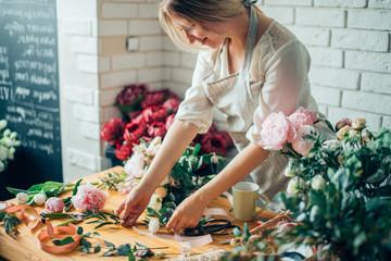 Nasmijana dražesna mlada žena cvjećar koja uređuje biljke u cvjećarnici