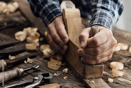 Photo Carpenter working in his workshop, he is smoothing a wooden board using a planer