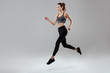 Side view full length portrait of a young fitness woman running