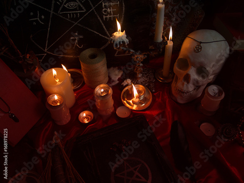 Witchcraft composition with human skull, burning candles, magic book, amulets and pentagram symbol Poster
