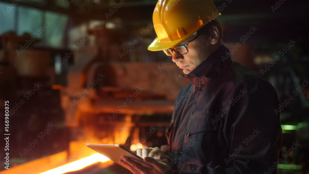 Fototapety, obrazy: Engineer in Glasses using Tablet PC in Foundry. Industrial Environment.