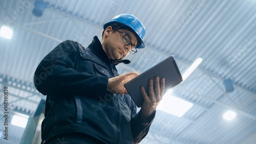 Fotografia  Factory worker in a hard hat is using a tablet computer.