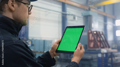 Fotografia  Footage of a tablet with green mock-up screen being used by a worker in industrial environment in a factory
