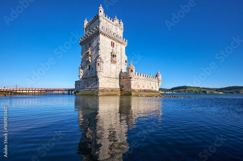 Belem Tower on river Tagus in Lisbon with reflection in water on blue sky backgr Canvas Print