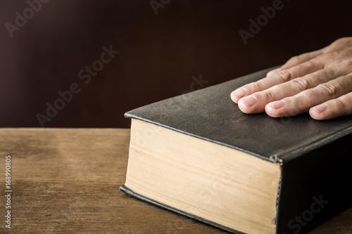 Fotografia  Man's hand swearing on the bible. Taking an oath.