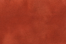 Background Of Dark Orange Suede Fabric Closeup. Velvet Matt Texture Of Ginger Nubuck Textile