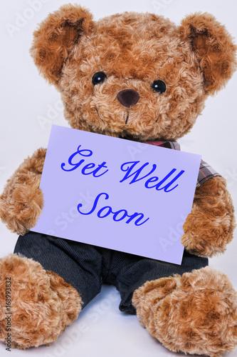 Fotografie, Obraz  Teddy bear holding a purple sign that says Get Well Soon