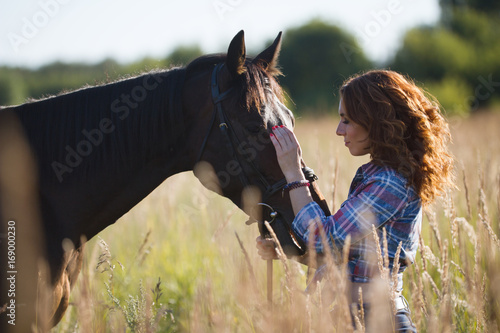 Fototapeta Young woman and horse in the meadow at summer evening obraz