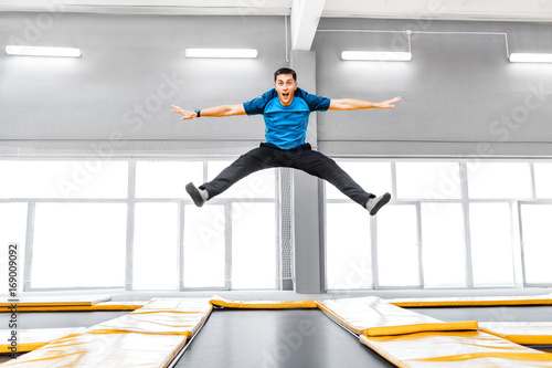 Fotografía  A young fit happy man jumping and flying on trampoline in fitness gym