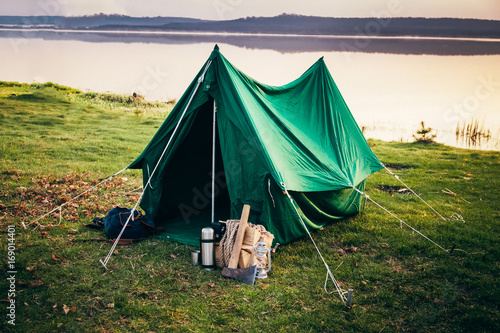 Obraz Green tent standing on the coast of the lake in the misty mornin - fototapety do salonu