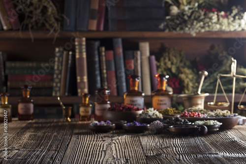 Natural medicine. Shallow depth of focus. Wooden table. Herbs, berries and flowers in bowls. Beautiful bokeh.