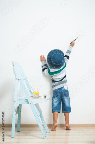 szczesliwe-dziecko-malujace-farbkami-sciany-w-domu
