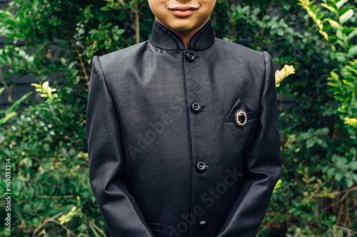 Smiling Indian boy wearing a traditional wedding outfit