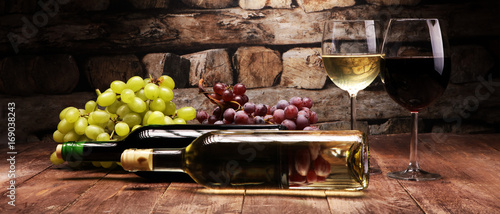 Fototapeta Red Wine bottle and white wine with grapes and glasses on wooden background obraz