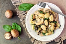 Gnocchi With A Mushroom Cream Sauce, Spinach, Chicken And Sun Dried Tomatoes, Above Scene On A Dark Stone Background