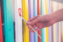 Woman Draw Heart On Colorful Fence With Painting Brush