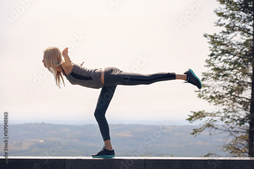 Fit woman balance workout outdoor, stretching exercises,yoga, pilates, sport, fitness, active lifestyle concept