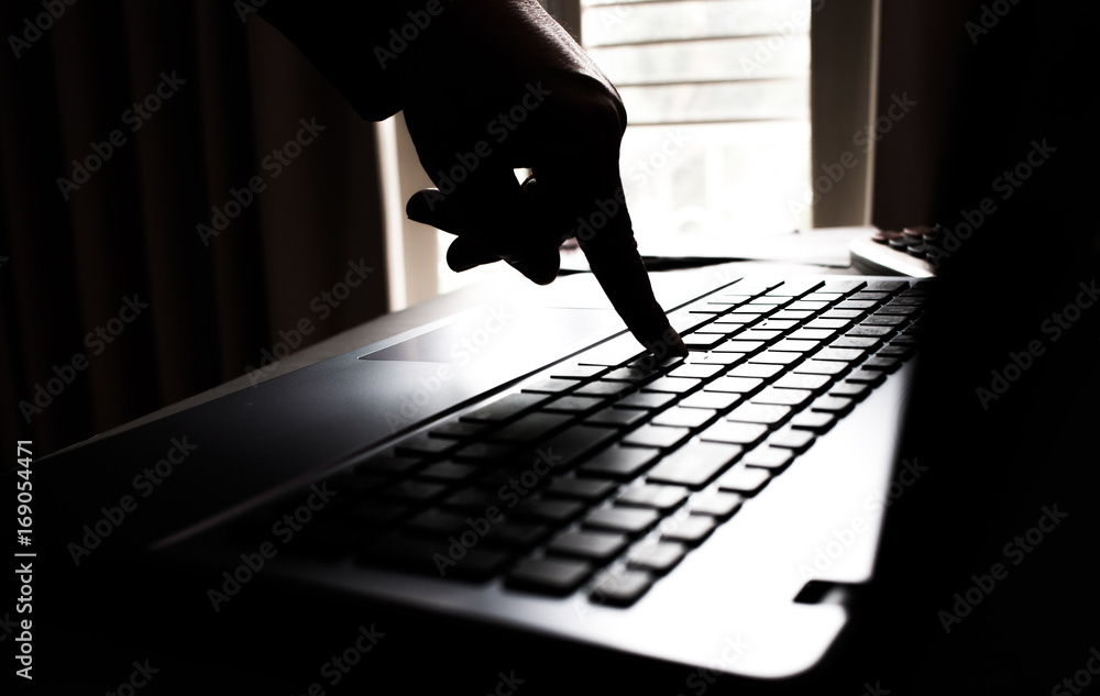 Silhouette black and white hands of anonymous hackers typing code on keyboard of laptop for remotely reach and receiving personal information online networking, Internet Crime Payment Security Concept