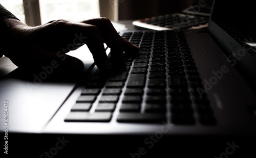 Fototapety, obrazy: Silhouette black and white hands of anonymous hackers typing code on keyboard of laptop for remotely reach and receiving personal information online networking, Internet Crime Payment Security Concept