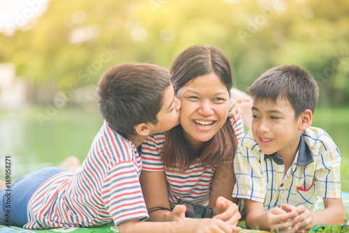 Little boys kissing his single mom at the park Canvas-taulu