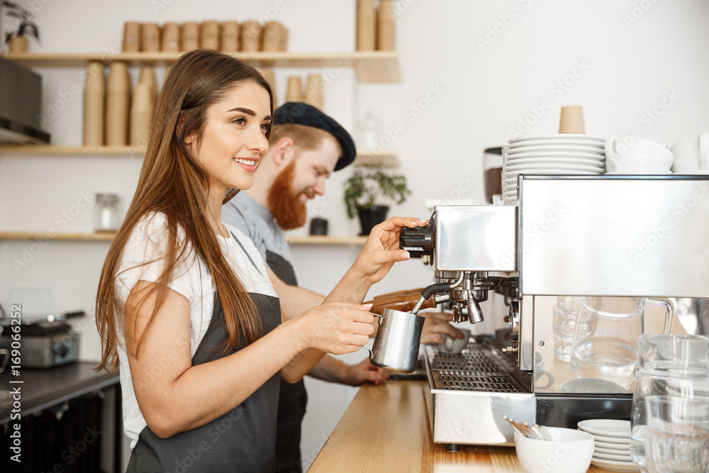 Fototapeta Coffee Business Concept - portrait of lady barista in apron preparing and steaming milk for coffee order with her partner while standing at cafe.