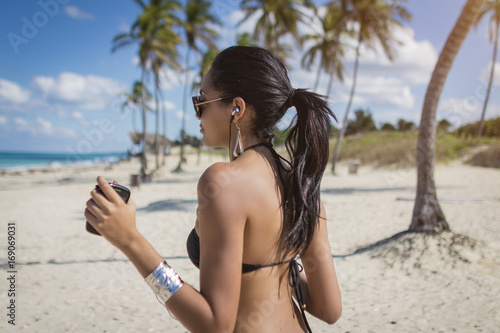 Cuban girl with smartphone dancing on the beach with palms, Cuba Canvas Print