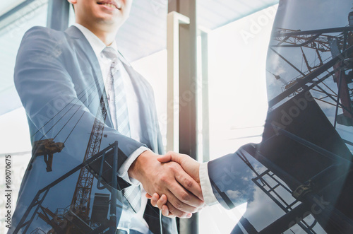 Photo Double exposure of two businessmen reaching an agreement and making handshake with abstract construction site - Greeting and dealing real estate business concepts