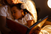 Little Daughter Fell Asleep At Mom While Reading Book