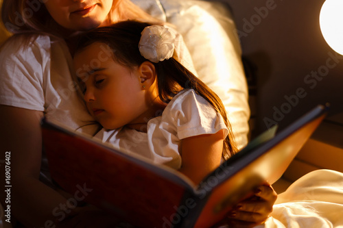 Little daughter fell asleep at mom while reading book Canvas Print