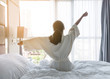 Leinwanddruck Bild - Easy lifestyle young Asian girl waking up in the morning taking a rest relaxing in hotel room for world lazy day concept