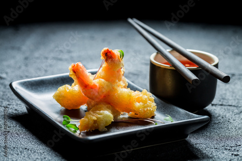 Hot shrimp in tempura with red sauce on black rock