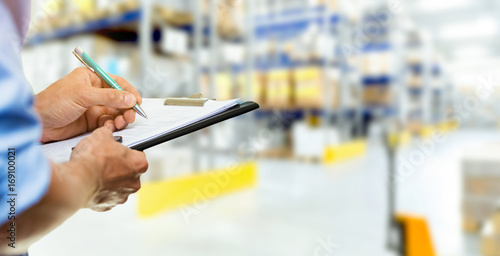 Fotografía  logistics service man writing documents on clipboard in warehouse