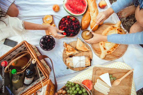 Fotografie, Obraz Picnic set with fruit, cheese, toast, honey, wine with a wicker basket and a blanket