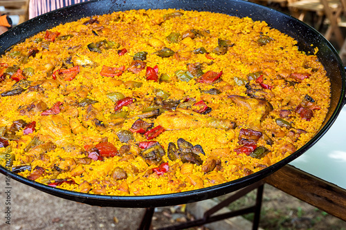 Fotografiet Large flat frying pan with cooked homemade Spanish paella with variety of meats, vegetables, rice, tomato sauce, spices