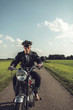 Vintage motorcyclist riding on country road in summer.