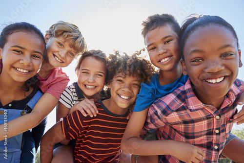 Fényképezés  Six pre-teen friends piggybacking in a park, close up portrait