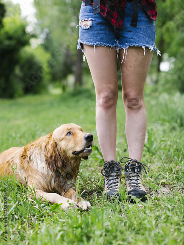 Dog lying beside young woman in shorts