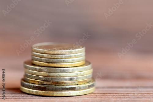 Tower of coins isolated on a wood background  Financial concept