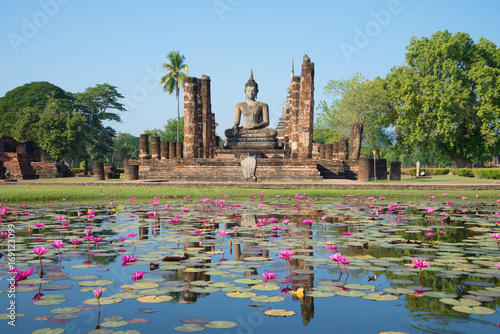 Foto  Ruins of ancient Buddhist temple Wat Chana Songkram on the shore of a lake with pink lilies