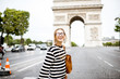 Young business woman in striped sweater crossing street near the famous triumpal arch in Paris