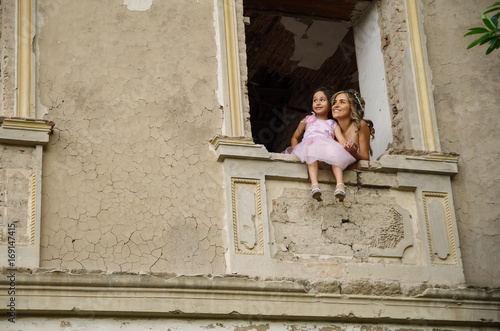 Poster de jardin Havana Beautiful woman and her cute little daughter smiling, wearing a pink princess dress, posing in a window castle while the little girl is sitting in the window