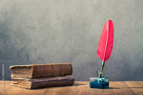 Vintage red quill pen with inkwell and old books on wooden table front concrete wall background. Retro instagram style filtered photo