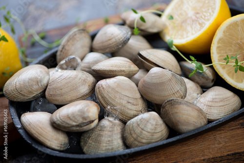 Close-up of fresh unopened vongole shells with lemon, selective focus, shallow depth of field, horizontal shot